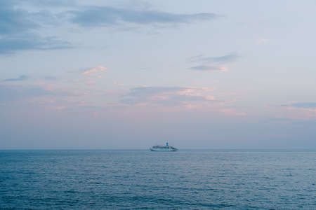 A small cruise liner sails in the open sea against the sunset sky with orange clouds. Stok Fotoğraf