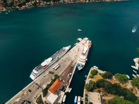 Aerial shot from the drone - two liners moored on the pier near the old town of Kotor, in the Gulf, Montenegro. Top view.
