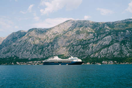 A huge multi-deck cruise liner in Kotor Bay, against the backdrop of a mountain above the city of Dovrota and Ljuta in Montenegro.
