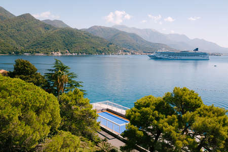 The cruise liner sails into the Bay of Kotor against the backdrop of the mountains above the town of Tivat in Montenegro. Stok Fotoğraf