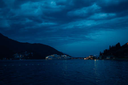 Cruise liner at night, against the backdrop of mountains and cloudy sky with clouds.