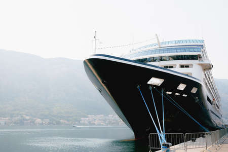 The nose of a close-up cruise liner moored on a jetty near the old town of Kotor in Montenegro. In the Bay of Kotor, against the backdrop of mountains and cloudy sky.