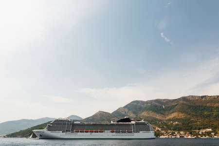 A large liner in the Gulf of Kotor in Montenegro, against the backdrop of a mountain.