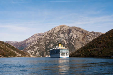 A tall, high-rise huge cruise liner in the Verige Strait, in the Boka Kottorska - Kotor Bay in Montenegro, against the backdrop of the city of Perast.