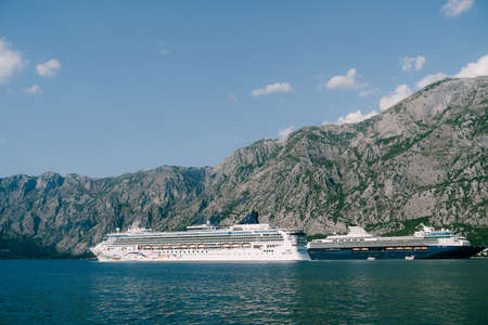 Two huge cruise liners in Kotor Bay in Montenegro, against the backdrop of rocky mountains and blue sky. Near the cities of Dobrota and Ljuta. Stok Fotoğraf