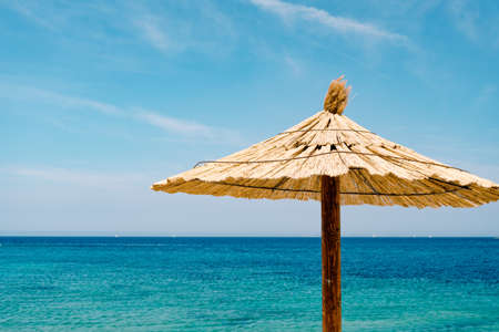 A beach thatched umbrella against the blue sky and azure water on a sandy beach in Croatia, in the city of Primosten.