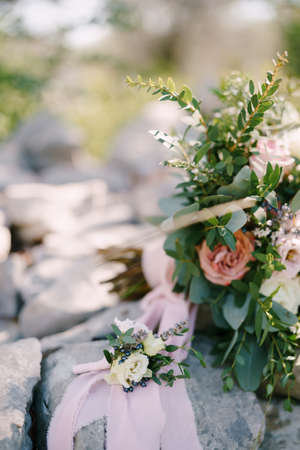 The grooms budier of white flowers against the background of a bouquet, stone and pink ribbon