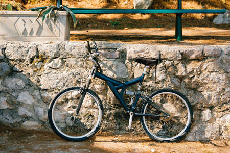 Blue bike by the stone curb on the street Stok Fotoğraf