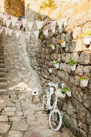 White decorative bike against the wall with pots for flowers and flags.