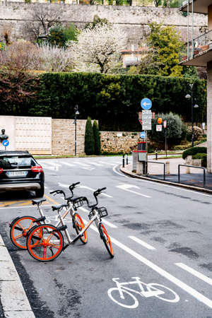 Bicycle parking in the middle of the road by green spaces and a brick fence Stok Fotoğraf