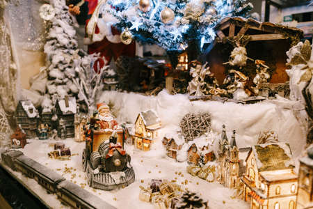 Showcase decor for the New Year and Christmas with figures, beads and a Christmas tree.