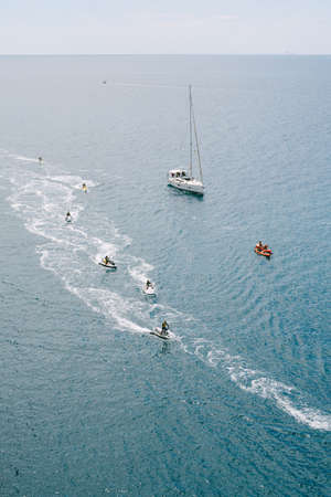 White yacht on calm blue water with jet skis in a row. Stok Fotoğraf
