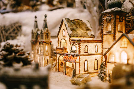 Christmas decor of a toy house with lighting in a shop window.
