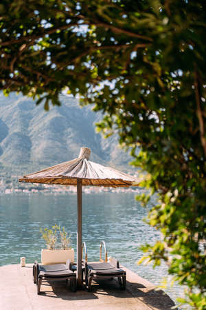 Lounges on the dock near the sea under a thatched beach umbrella.