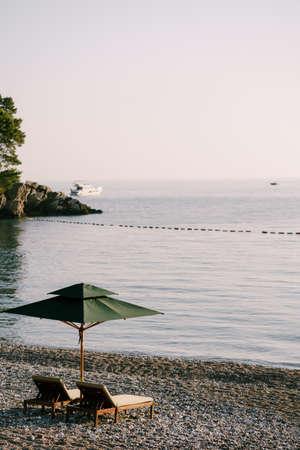 Luxurious wooden sun loungers and green beach umbrellas, on a sandy beach in Milocer Park, near Stefan Island, Montenegro.
