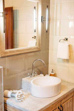 White washbasin with large mirror, towel holder and LED lamp in the bathroom with white tiles. Stock Photo