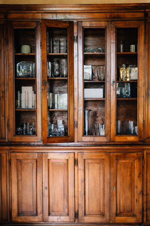 An old wooden cupboard with doors that can be locked with keys and a shallow grate for glass. Archivio Fotografico