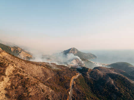 The city on the coast of Montenegro is engulfed in fire. White smoke over the city, the road and the mountains. Banco de Imagens
