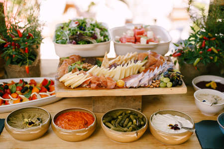 Deep platter of appetizers on the table with cutting board with cold meats and cheese and caprese and salad trays.