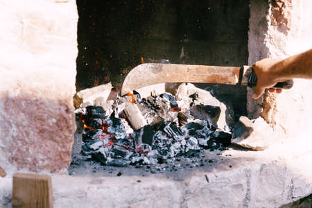 The chef places burning coals in the grill with a machete. Banco de Imagens