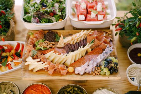 Slicing of cheeses and meat delicacies on the table with vegetable dishes and bitter pepper bushes.