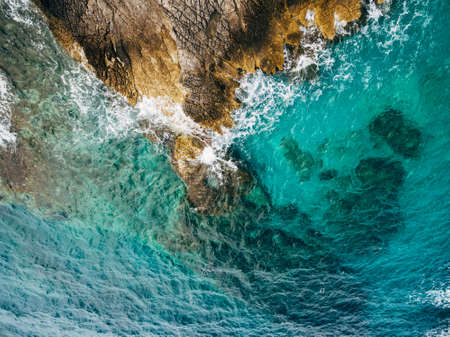 Blue azure sea water, white frothy waves hitting the rocky shore, aerial top view.