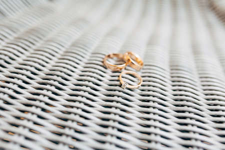 Wedding rings of gold and a ring for the bride with a precious stone on a gray background.