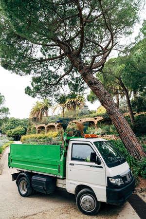 Barcelona, Spain - 12 may 2020: White-green medium-duty commercial mini-truck. Gardener car in the park.