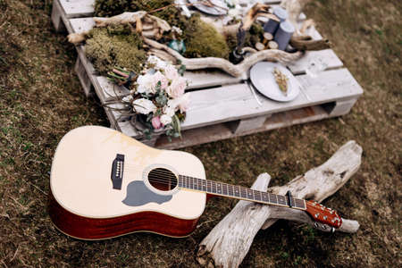 Acoustic guitar on the grass and flowers, a tree branch and candles on a wooden stand.