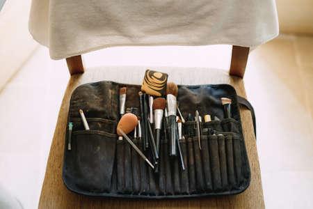 Black work beautician cosmetic bag with makeup brushes, sponge and eyebrow tweezers on wooden chair. Foto de archivo
