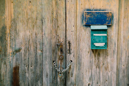 An old green mailbox on a dilapidated wooden gate with a chain wrapped handle and a padlock.