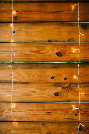 Wooden planks wall close-up in a horizontal position with garlands.