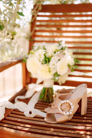 Beige clogs with a round buckle on a wooden chair with a bouquet of white flowers tied with a ribbon.