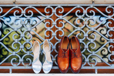 New brown mens shoes with womens white sandals on the window at the metal grille outside. Stock Photo