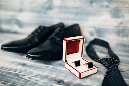 Black leather mens shoes with box cufflinks and polka dot tie on wood texture with shallow depth of field. Stock Photo