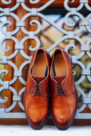 New brown mens shoes by the window with metal bars with shallow depth of field. Stock Photo