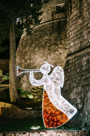 Christmas city street decorations - an angel made from a bright garland of led lanterns.