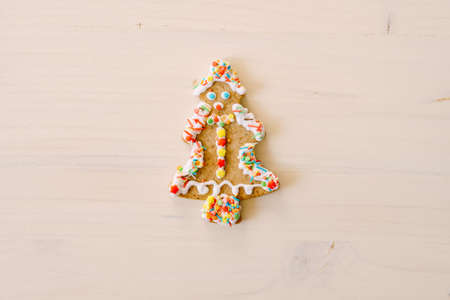 Gingerbread cookies in the shape of a Christmas tree, decorated with glaze and colored sprinkles, on a white painted wood texture. 스톡 콘텐츠