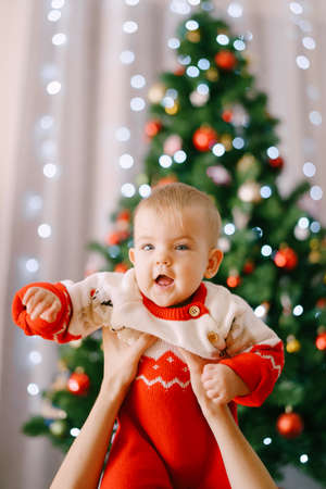 Toddler in a red-and-white Christmas bodysuit in her mothers arms in front of a Christmas tree