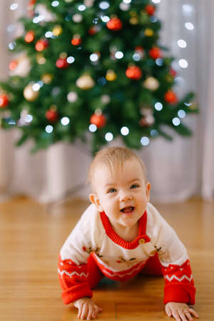 Baby girl in a Christmas-themed costume is crawling in front of a Christmas tree