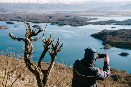 A man photographs Slansko Lake in Niksic, Montenegro with his mobile phone, against the backdrop of snow-capped mountains.