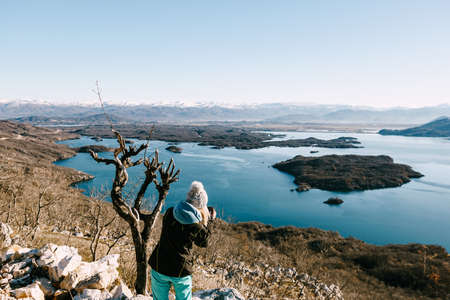 Girl photographer photographs Niksic lake and snow-capped mountains. Imagens - 156868911