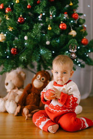 Toddler in a red and white Christmas  is holding an apple in front of a Christmas tree 스톡 콘텐츠