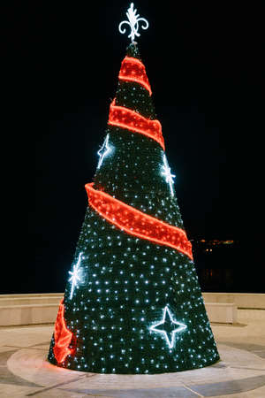 A cone-shaped Christmas tree decorated with garlands in the town square.