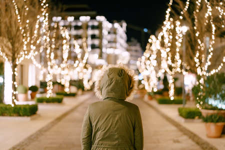 A girl in a hood with fur stands on a street decorated for Christmas in the city. 스톡 콘텐츠