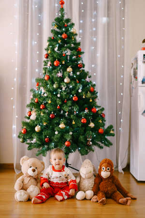 Toddler is sitting next to her stuffed toys in front of a Christmas tree 스톡 콘텐츠