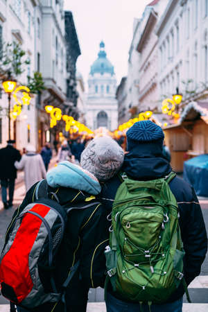A couple of tourists with backpacks walk the streets of Budapest, decorated for Christmas, against the background of St. Stephens Basilica.