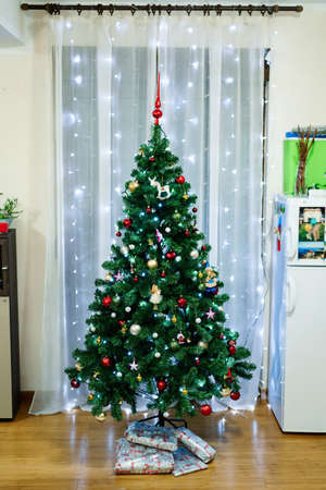 A beautiful full-length Christmas tree in the interior of the room. 스톡 콘텐츠