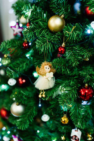 Little toy angel on the branches of a Christmas tree.