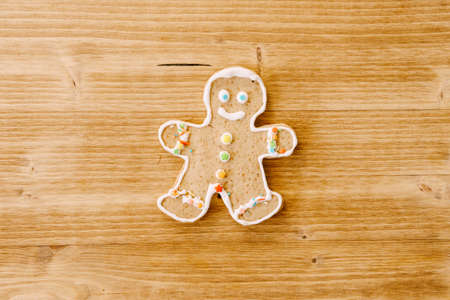 Christmas cookies gingerbread man on a wooden texture.